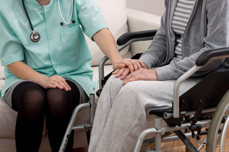Doctor talking with aged woman on wheelchair