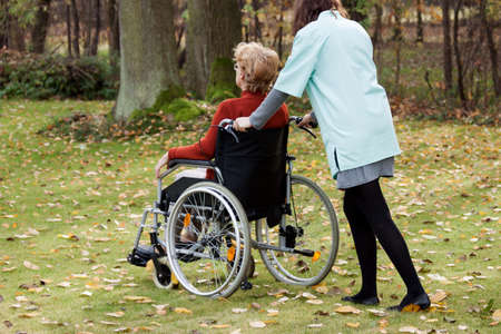 Carer walking in the park with elderly woman on wheelchair Stock Photo