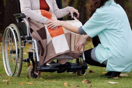 Jonge verpleegster vol mededogen voor de dame met een handicap Stockfoto