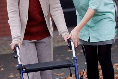 mobility nursing: Carer teaching elder lady using a walker