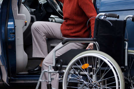 Handicapped elder woman getting into a car Stock Photo