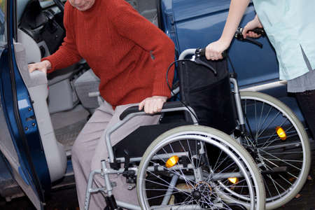 just arrived: Nurse offering a wheelchair to elder lady who has just arrived to hospital Stock Photo