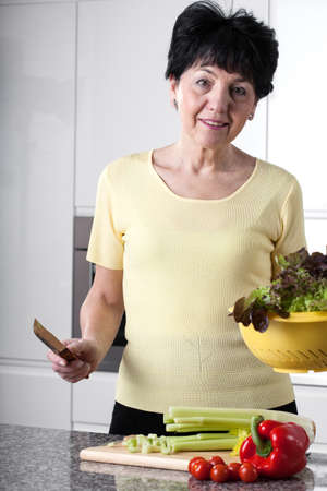 pices: Elder woman is preparing meal in kitchen