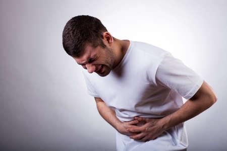 dolor abdominal: Hombre joven con dolor de estómago severo sosteniendo su estómago