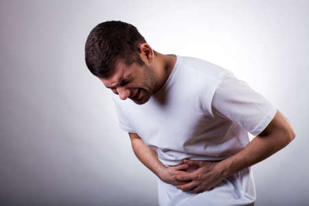 Young man with severe stomachache holding his stomach photo