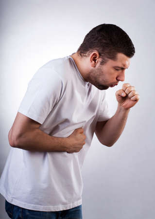cough medicine: Strongly coughing young man suffered from asthma Stock Photo