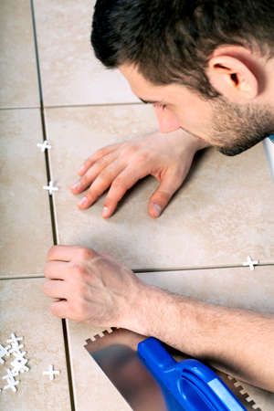 Young man laying tiles on the floor photo