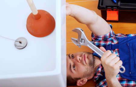 hydraulic: Young handy man repairing sink in a bathroom Stock Photo