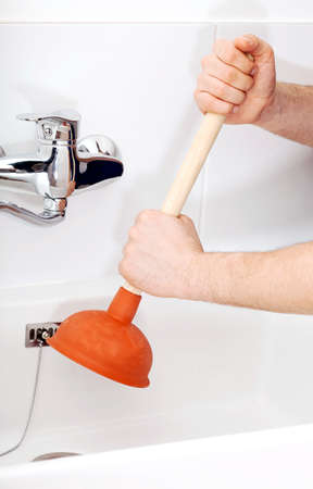 unblock: Vertical view of a handy mans hands with plumber Stock Photo