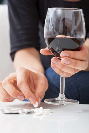 narcotism: Woman taking a lot of pills with wine Stock Photo