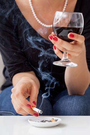 drinking problem: Woman wearing pearls smoking cigarette and drinking wine