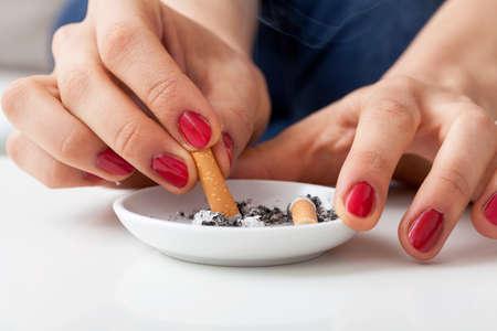재떨이에 완성 된 담배 퍼팅 여자