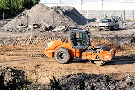 steamroller: An orange steamroller working on a construction site