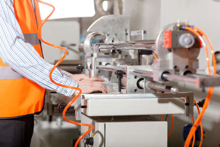 Factory worker operating lathe during production process photo