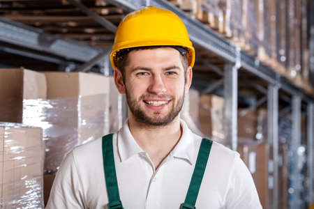 Young worker wearing helmet in factory warehouse photo