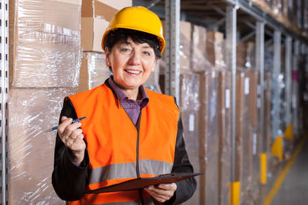 shelve: Female manager taking notes in factory warehouse