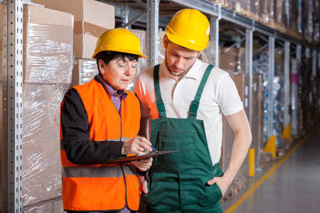 shelve: Female manager giving worker advice in warehouse Stock Photo
