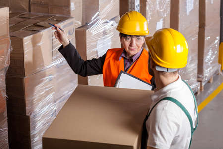 warehouseman: Manager giving worker instruction about loads storage in warehouse