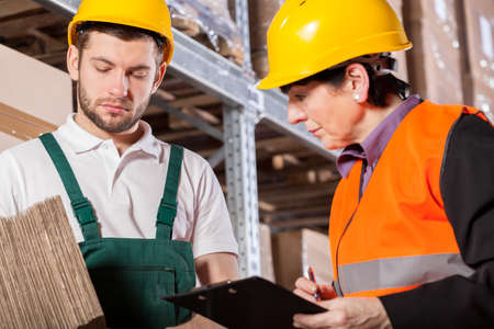 engineering clipboard: Worker consulting storage details with manager in warehouse Stock Photo