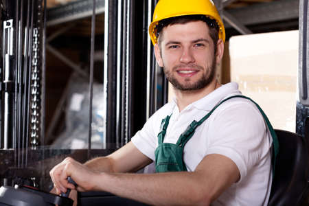 warehouseman: Storehouse worker driving on forklift in warehouse