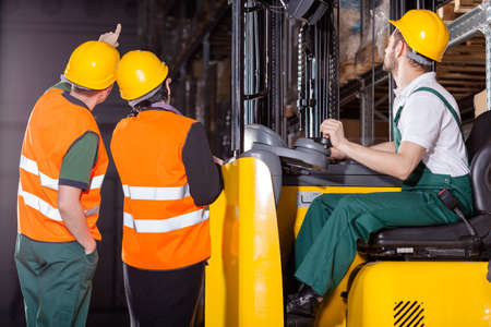 Worker operating forklift in warehouse with supervisors photo