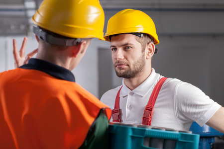 Young worker consulting with manager in factory
