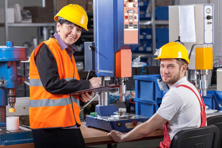 industrial workers: Production worker at workplace and his supervisor Stock Photo