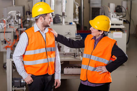 warehouseman: Smiling employees discussing at production area,horizontal Stock Photo