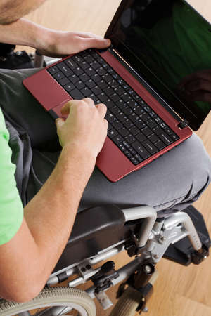A laptop being used by a man on a wheelchair photo