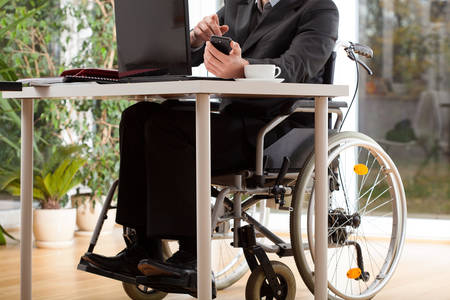 A businessman on a wheelchair working in his office photo