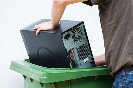 throwaway: Men throwaway hardware into container Stock Photo