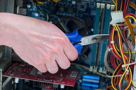 redes electricas: Los hombres usan pinzas para cortar cables de la computadora