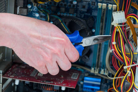 use computer: Men use pliers to cut computer cables
