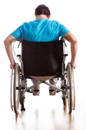 suffer: A backside of a man driving a wheelchair