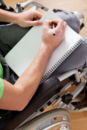 Young man sitting on wheelchair with notebook and pen photo