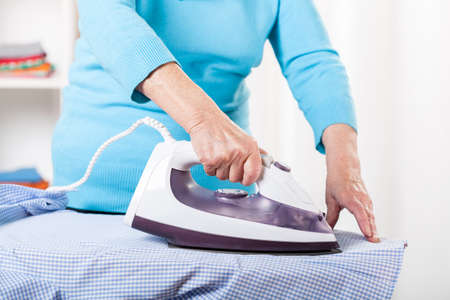Elderly lady during ironing shirt at home photo