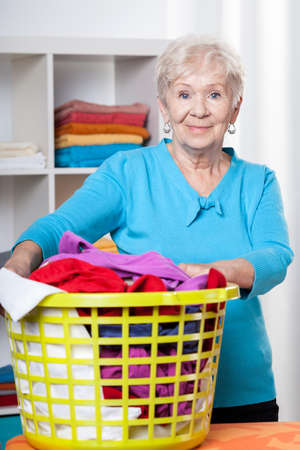 Elderdly lady with washing in laundry basket photo