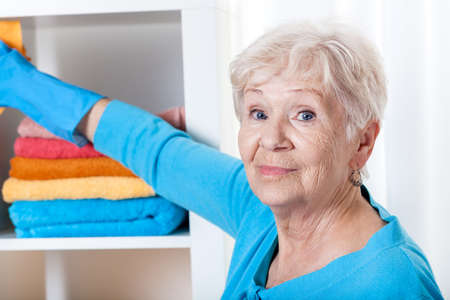 Smiling senior woman during household chores,horizontal photo