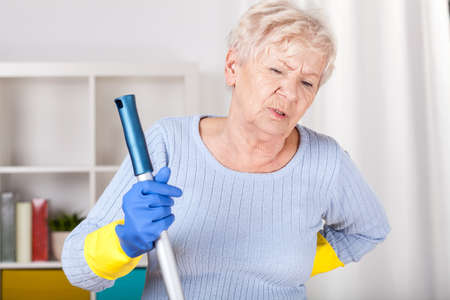 Senior woman with backache during cleaning