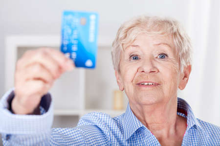 Modern senior lady with credit card, horizontal photo