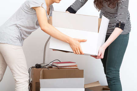 Two women moving heavy and white boxes Banco de Imagens