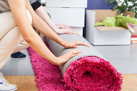 carpet clean: People rolling a fuzzy pink carpet while packing Stock Photo