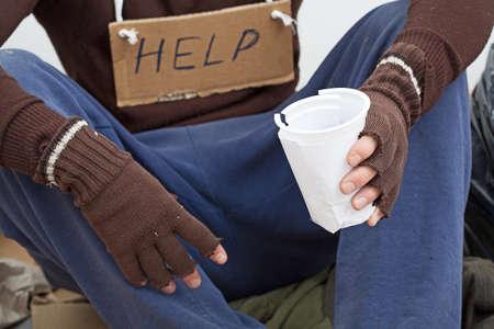 limosna: Sin hogar con la taza de papel a la espera de la limosna en la calle