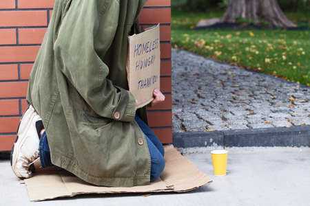 Beggar sitting on the corner asking for money and for food photo
