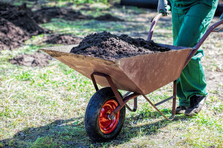 blue collar: Worker with a wheelbarrow full of compost Stock Photo