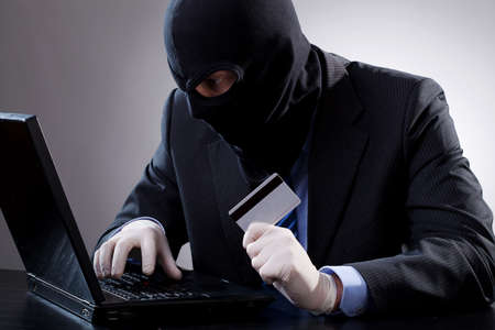 Hacker holding a credit card and using  computer photo