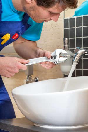 Close up of plumber repairing broken faucet Фото со стока