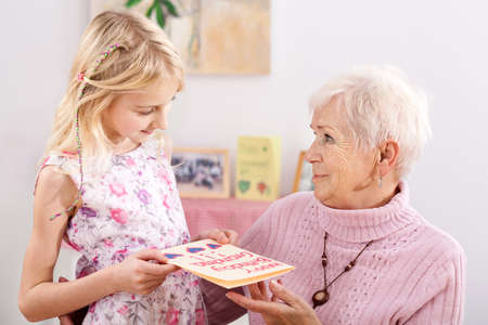 grandmother and children: Granddaughter giving birthday drawing for special occasion