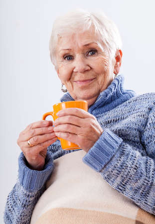 Grandmother with cup of ea on white isolated background photo