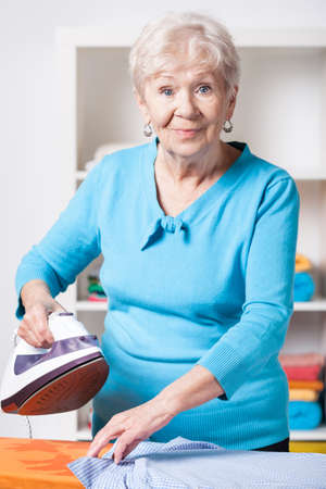 Elderly woman ironing shirt on the ironing board photo